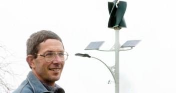 Chris Teo-Sherrell with the recently erected solar and wind powered street light
