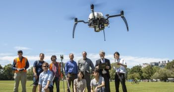 Yokohama National University and UC academics and students, including UC WRC Research Leader Dr Graeme Woodward (standing centre) and Professor Ryuji Kohno (standing second from right) watch while UC Senior Research Engineer Kelvin Barnsdale (far left) controls a UC drone